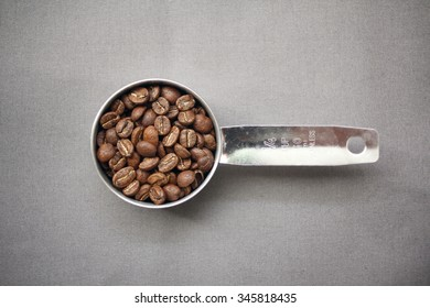 Coffee Beans Whole in a Stainless Steel Measuring Cup with Grey Background