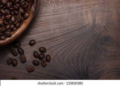coffee beans and wooden bowl on the brown table