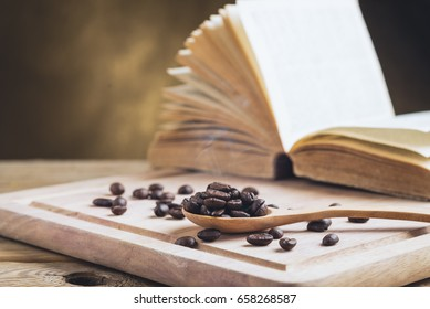 coffee beans in wooden spoon with old book on wood table.