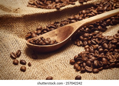 Coffee beans and wooden spoon on sackcloth surface