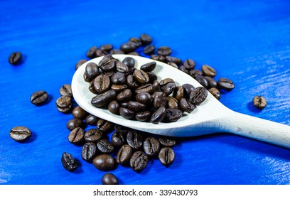 Coffee beans in wooden spoon on blue background