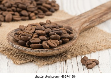 Coffee beans in a wooden spoon on old wooden table. Selective focus.