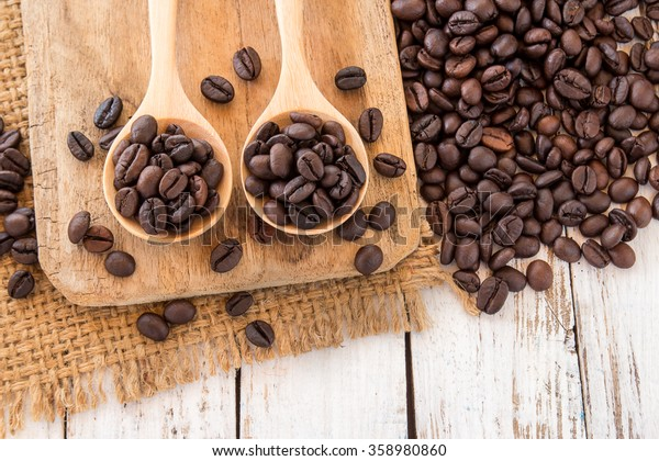 Coffee beans in wooden spoon on a wooden background