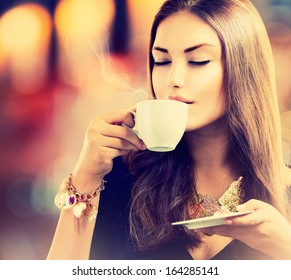 Coffee. Beautiful Girl Drinking Tea or Coffee in Cafe. Beauty Model Woman with the Cup of Hot Beverage. Warm Colors Toned