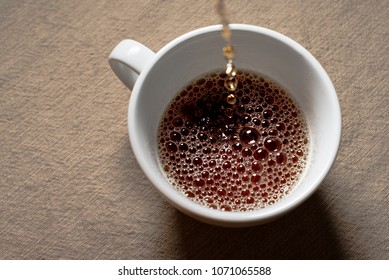 Coffee being poured into a white coffee cup.