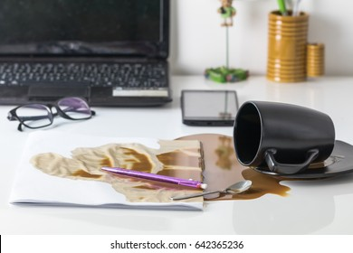 Coffee in black cup spilled on the table in the morning working day