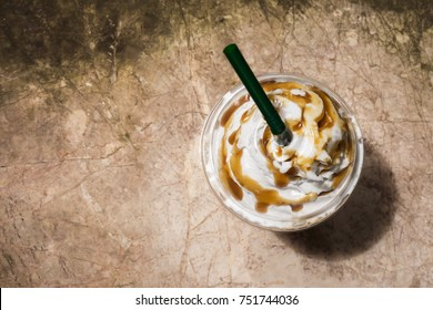 Coffee blend in plastic cup. Served with whipped cream topping and sweet syrup. Favorite caffeine beverage. Top view with copy space.