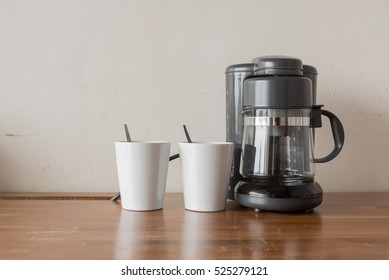 Coffee blender and boiler with coffee cups on table top