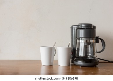 Coffee blender and boiler with coffee cups on wooden table top