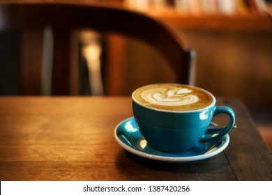 Coffee in blue cup on wooden table in cafe with lighting background