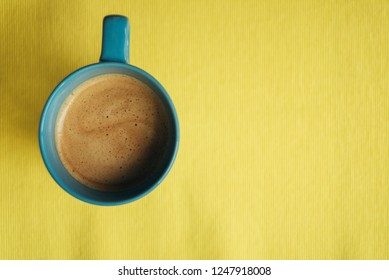 Coffee in a blue cup on a yellow background