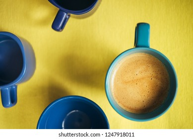 Coffee in a blue cup on a yellow background with empty cups