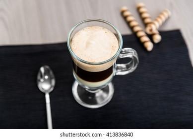 Coffee Bombon and wafer rolls on a dark napkin