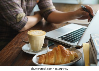 Coffee, bread on the desk with notebook, breakfast