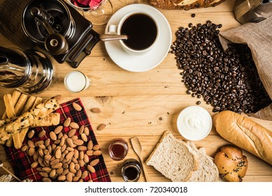Coffee break concept. Copyspace. White coffee cup with coffee decoration and bread and almond on wooden background.