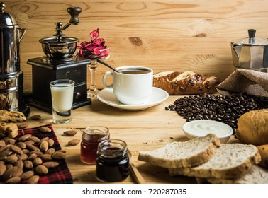 Coffee break concept. White coffee cup with coffee decoration and bread and almond on wooden background.