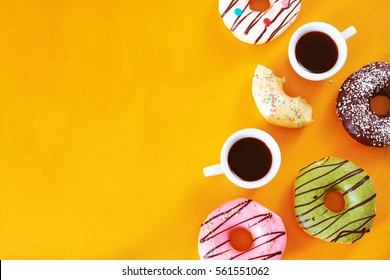 Coffee break with donuts assorted. Pistachio, chocolate, vanilla, strawberry donuts and two cups of espresso over yellow background. Copy scape.