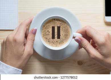 Coffee break. Female hands touches white cup of classic coffee, top view, close up. Pause icon on foam. Pause, break, short breather, relax, pit stop in the middle of business life.