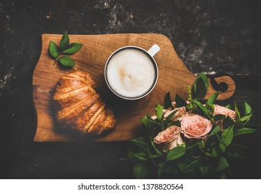Coffee break. Flat-lay of cup of hot cappuccino with croissant and bouquet of pink flowers over black shabby background, top view. Spring mood
