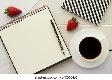 Coffee break,  home office desk, ideas, notes, plan writing or sketching  concept. Open notebook, sketchbook or scrapbook with blank page, coffee cup and strawberries on white wooden table.  Top view.