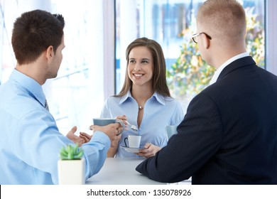 Coffee break in office, coworkers enjoying free time and conversation, smiling.