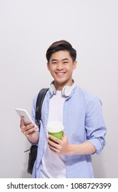 Coffee break. Positive handsome high school student holding a smartphone and drinking coffee while standing against grey wall