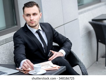 Coffee Break. Successful and confident businessman sitting at the table drinking coffee and reading a financial newspaper. Young man in formal clothes working on a laptop