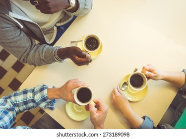 coffee break. three friends sitting and having a coffee in a store. concept about people, coffee, and bars