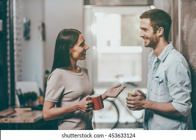 Coffee break. Two cheerful young people holding coffee cups and talking while standing in office