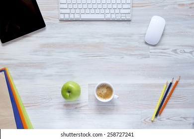 Coffee break. Well organized workspace on the wooden table with tablet PC, keyboard and mouse, color pencils, coffee mug along with green apple and some booklets