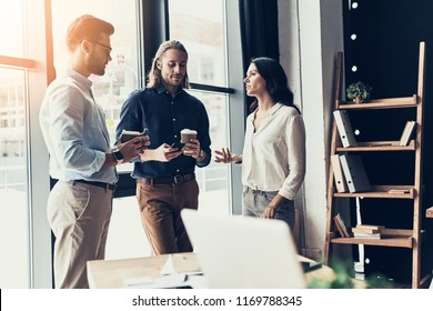 Coffee break. Young colleagues in smart casual wear discussing something and holding disposable cups while standing in the office