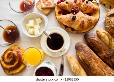 Coffee for breakfast with croissants, butter, bread and orange juice at white napkin