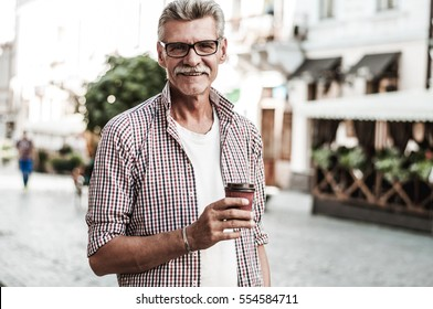 It's coffee break.Portrait of attractive men in casual clothes walk on the street.