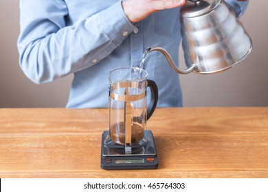 coffee brewing, step by step. Barista prepares coffee french press. The process of pouring water into french press