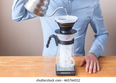 coffee brewing, step by step. Barista gently pours hot water on the surface of the ground coffee. Wetting the coffee