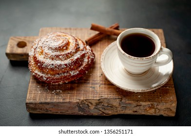 coffee with a bun on a cutting board on a background of stone, morning breakfast