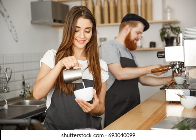 Coffee Business Concept - close-up lady barista in apron preparing and pouring milk into hot cup while standing at cafe.