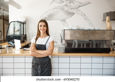 Coffee Business owner Concept - attractive young beautiful caucasian barista in apron smiling at camera in coffee shop counter.