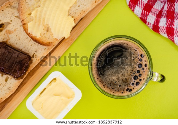 Coffee with butter toast and strawberry jam, on a green tablecloth, viewed from above