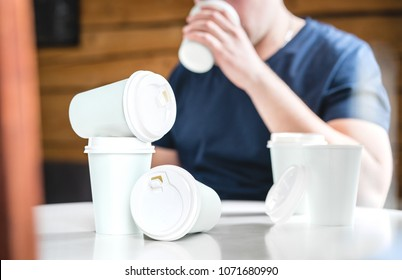 Coffee or caffeine addiction concept. Addicted or thirsty man drinking too much. Addict with many empty take away paper cups on table. Trying to stay awake.