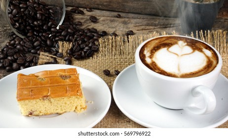 Coffee and cake. A cup of latte, cappuccino or espresso coffee with milk put on a wood table with dark roasted coffee beans