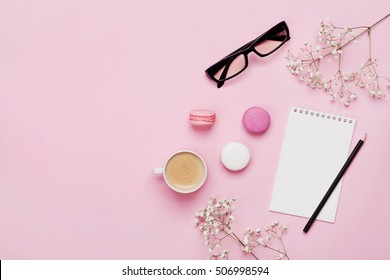 Coffee, cake macaron, clean notebook, eyeglasses and flower on pink table from above. Female working desk. Cozy breakfast. Flat lay style.
