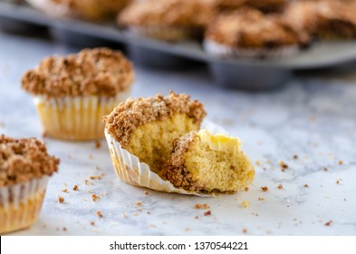 A coffee cake muffin, with a bite taken out on a table with muffin tin in background.  Horizontal