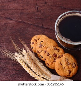 Coffee and cake on brown wooden table background.