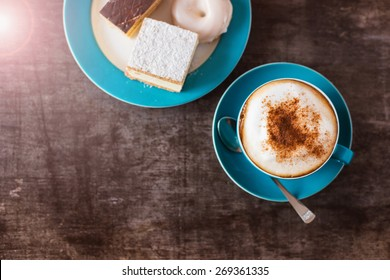 Coffee and cakes on a wooden table background