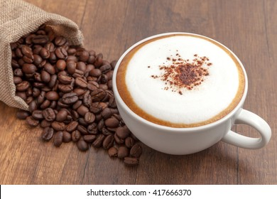 Coffee cappuccino and coffee beans on wooden background