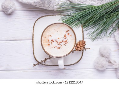 Coffee cappuccino with ceylon cinnamon, a branch of a pine tree and knitted accessories on a white wooden background. Free space