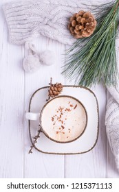 Coffee cappuccino with ceylon cinnamon, a branch of a pine tree and knitted accessories on a white wooden background. Top view, free space