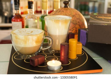 coffee and cappuccino in cups on the playing table against the background of the globe and bottles