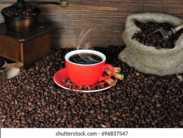 Coffee, cappuccino or espresso smoke and cinnamon sticks on a wooden table with a coffee grinder